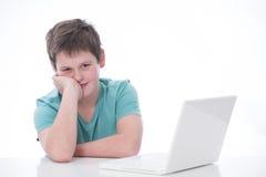 Muchacho joven con la computadora portátil Imagenes de archivo