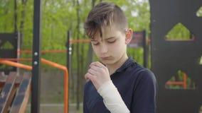 Muchacho joven con la mano vendada en el patio El niño quiere jugar pero lo hieren almacen de metraje de vídeo