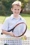Muchacho joven con la raqueta en la sonrisa del campo de tenis Imágenes de archivo libres de regalías
