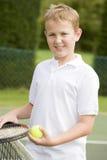 Muchacho joven con la raqueta en la sonrisa del campo de tenis Fotos de archivo