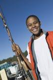 Muchacho joven con las cañas de pescar Imagen de archivo libre de regalías