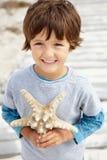 Muchacho joven con las estrellas de mar Fotos de archivo libres de regalías