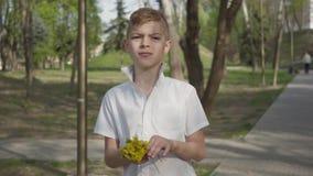 Muchacho joven con las flores del diente de le?n que esperan para dar un ramo para la persona Reconstrucci?n al aire libre almacen de video