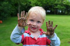 Muchacho joven con las manos fangosas Fotos de archivo libres de regalías