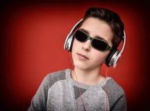 Muchacho joven con los auriculares que disfruta de música Foto de archivo libre de regalías