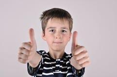 Muchacho joven con los pulgares para arriba Fotos de archivo