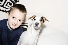 Muchacho joven con su perro que se sienta en el sofá Imágenes de archivo libres de regalías
