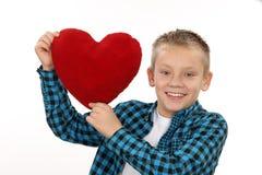 Muchacho joven con un corazón rojo el día de tarjeta del día de San Valentín Fotos de archivo
