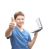 Muchacho joven con un pequeño ordenador portátil Fotos de archivo