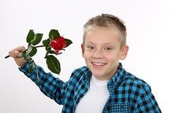 Muchacho joven con una rosa el día de tarjeta del día de San Valentín Fotografía de archivo