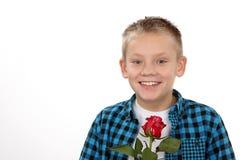Muchacho joven con una rosa el día de tarjeta del día de San Valentín Foto de archivo libre de regalías