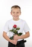 Muchacho joven con una rosa el día de tarjeta del día de San Valentín Fotos de archivo libres de regalías