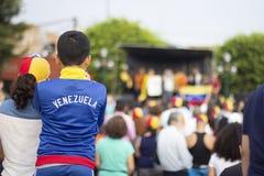 Muchacho joven con venezolano mirando una etapa en la protesta venezolana imagen de archivo