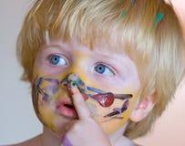 Muchacho joven cubierto en pintura de la cara Imágenes de archivo libres de regalías