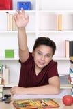 Muchacho joven del adolescente con la mano aumentada en la escuela Foto de archivo