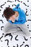 Muchacho joven del adolescente con las porciones de preguntas Foto de archivo libre de regalías