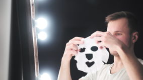 Muchacho joven del adolescente de la belleza que aplica la mascarilla cosmética y que se admira en el espejo metrajes