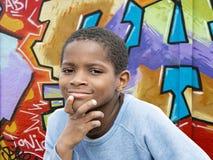 Muchacho joven del Afro delante de una pared de la pintada Fotos de archivo