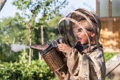 Muchacho joven del apicultor que usa a un fumador en yarda de la abeja Imágenes de archivo libres de regalías