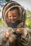 Muchacho joven del apicultor que usa a un fumador en yarda de la abeja Foto de archivo libre de regalías