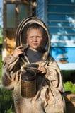 Muchacho joven del apicultor que usa a un fumador en yarda de la abeja Fotos de archivo