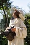 Muchacho joven del apicultor que usa a un fumador en yarda de la abeja Fotografía de archivo