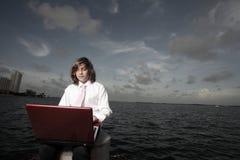 Muchacho joven del asunto en una computadora portátil Imagenes de archivo