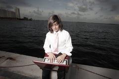Muchacho joven del asunto en una computadora portátil Imágenes de archivo libres de regalías