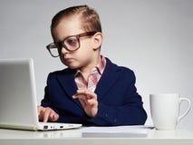 Muchacho joven del asunto Niño divertido en vidrios pequeño jefe en oficina imagen de archivo libre de regalías