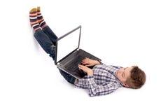Muchacho joven del empollón que miente en piso usando un ordenador portátil con el sc vacío del blanco Imagenes de archivo