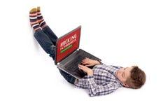 Muchacho joven del empollón que miente en piso y que corta usando un ordenador portátil Imágenes de archivo libres de regalías