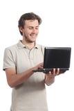 Muchacho joven del estudiante que hojea su ordenador del netbook Imagenes de archivo