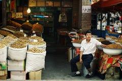 muchacho joven del uyghur en el mercado que vende nueces y especias y frutas secadas foto de archivo