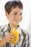 Muchacho joven dentro que bebe la sonrisa del zumo de naranja Fotografía de archivo libre de regalías