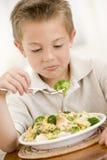 Muchacho joven dentro que come las pastas con brocolli Imagen de archivo