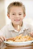 Muchacho joven dentro que come pescado frito con patatas fritas Fotos de archivo libres de regalías