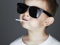 Muchacho joven divertido con una piruleta Niño de moda en gafas de sol Fotografía de archivo libre de regalías