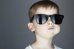 Muchacho joven divertido que come una piruleta Niño de moda en gafas de sol Fotos de archivo libres de regalías