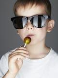 Muchacho joven divertido que come una piruleta Niño de moda en gafas de sol Foto de archivo libre de regalías
