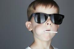 Muchacho joven divertido que come una piruleta Niño de moda en gafas de sol Fotos de archivo