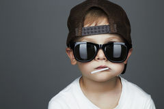 Muchacho joven divertido que come una piruleta Niño en gafas de sol imágenes de archivo libres de regalías