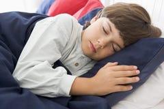 Muchacho joven dormido en su cama imagenes de archivo