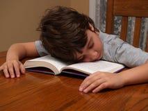 Muchacho joven dormido mientras que lee Foto de archivo libre de regalías