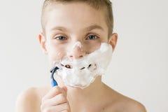 Muchacho joven emocionado que afeita con la maquinilla de afeitar plástica Fotografía de archivo libre de regalías