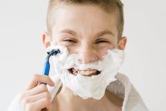 Muchacho joven emocionado que afeita con la maquinilla de afeitar plástica Imagen de archivo