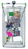 Muchacho joven en carretilla de las compras Imagen de archivo
