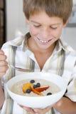 Muchacho joven en cocina que come la harina de avena con el SMI de la fruta fotografía de archivo
