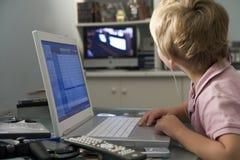 Muchacho joven en dormitorio usando la computadora portátil Imágenes de archivo libres de regalías