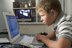 Muchacho joven en dormitorio usando la computadora portátil Imagen de archivo