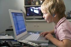 Muchacho joven en dormitorio usando la computadora portátil y el escuchar Fotografía de archivo libre de regalías